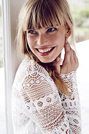 blonde woman with bangs smiling after cosmetic dentistry