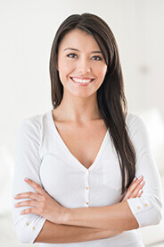 woman in white smiling after receiving porcelain veneers